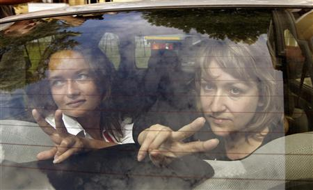 Belarussian journalists Irina Kozlik (L) and Yulia Darashkevich show victory signs from a police car near a court building in Minsk August 9, 2012. REUTERS/Vasily Fedosenko
