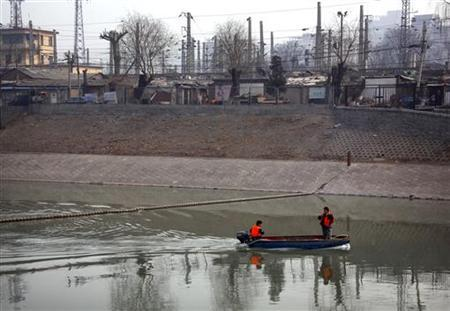 Rubbish collectors steer their boat along a polluted canal past a Hutong or ''small alley'' area which is being demolished in Beijing March 16, 2012. REUTERS/David Gray