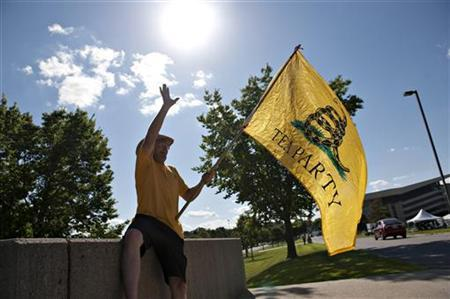 William DePorte of Council Bluffs, Iowa, waves to a passing vehicle as he waves a Tea Party flag outside a Republican Presidential Debate in Ames, Iowa, August 11, 2011. REUTERS/Daniel Acker