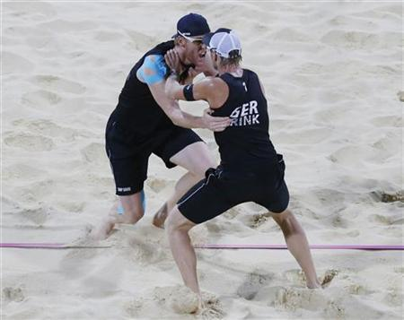 Germany's Jonas Reckermann (L) and Julius Brink celebrate victory in their men's beach volleyball gold medal match against Brazil's Alison and Emanuel at Horse Guards Parade during the London 2012 Olympic Games August 9, 2012. REUTERS/Dominic Ebenbichler