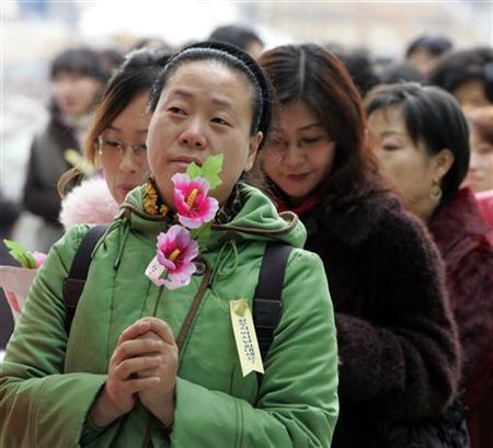South Korean women line up to hand over flowers called ''rose of Sharon'', the country's national flower, to the stem cell research team of Seoul National University, symbolising the submission of their intention to donate eggs for use in the research at the university in Seoul. REUTERS/Lee Jae-Won