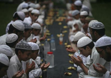 Muslims offer prayers before having their Iftar (fast-breaking) meal during the holy month of Ramadan at a madrasa or religious school on the outskirts of Jammu August 8, 2012. REUTERS/Mukesh Gupta