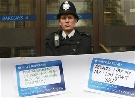 A police officer stands on duty as protestors from the Move Your Money group stick up posters on a branch of Barclays Bank in Westminster central London, July 4, 2012. REUTERS/Olivia Harris