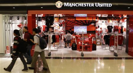 Shoppers walk past a Manchester United merchandise store at a mall in Singapore in this June 14, 2012 file photo. REUTERS/Tim Chong/Files
