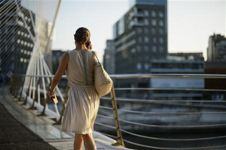 A woman crosses the Zubizuri (White Bridge) pedestrian bridge, designed by Spanish architect Santiago Calatrava, in front of the Torres Isozaki (by Japanese architect Arata Isozaki at dusk in Bilbao June 26, 2012. REUTERS/Vincent West