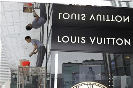 A worker makes preparations for the upcoming opening the largest Louis Vuitton store in China, which is located in Shanghai, July 17, 2012. REUTERS/Aly Song