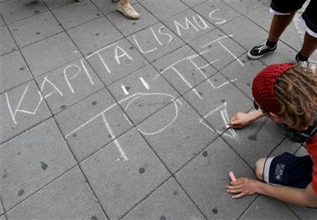 A protester writes ''Kapitalismus toetet'' (Capitalism kills) on a sidewalk during an anti-capitalism demonstration in downtown Frankfurt July 28, 2012. REUTERS/Ralph Orlowski