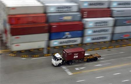 A container truck drives at a container area at the Yangshan Deep Water Port, near Shanghai March 23, 2012. REUTERS/Carlos Barria