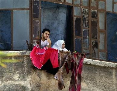 A man and a woman look out of a window in central Aleppo, August 10, 2012. REUTERS/Goran Tomasevic