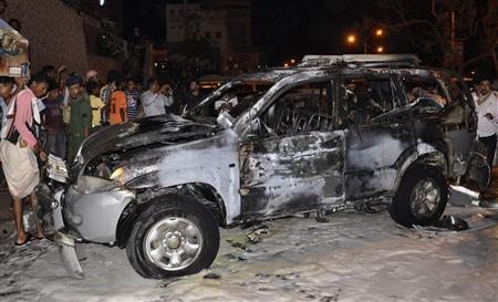 People look at the burnt car of Brigadier Omar Salim Ba-Rashid, the dean of the Military Academy after a blast ripped through it in the southern Yemeni port city of Mukalla August 9, 2012. REUTERS/Stringer
