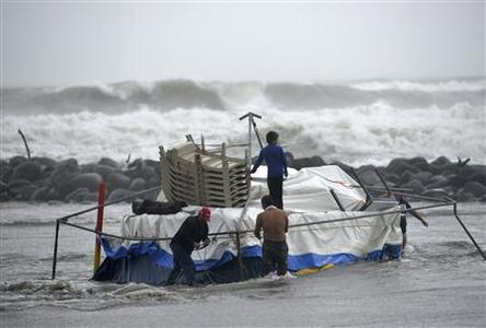People try to salvage the furniture of their food stand as it is being washed away by the flood in Boca Del Rio on the outskirts of Veracruz August 9, 2012.