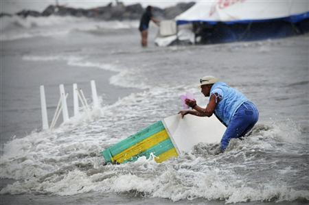 A woman tries to recover a piece of furniture that is being washed away by the flood in Boca Del Rio on the outskirts of Veracruz August 9, 2012.