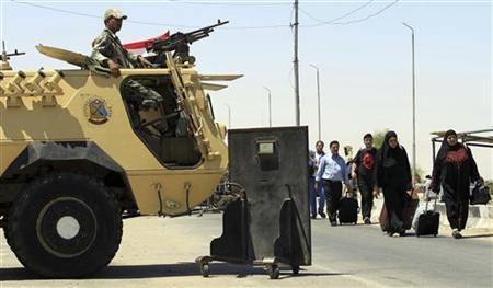 Palestinian travellers pass an Egyptian soldier standing guard on the Egyptian side of the Rafah border to cross over to Gaza at Rafah city, some 350 km (217 miles) northeast of Cairo August 10, 2012. REUTERS/Mohamed Abd El Ghany