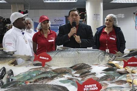 Venezuela's President Hugo Chavez (C) speaks during the opening of a state-run Bicentenario supermarket in Caracas August 8, 2012. REUTERS/Miraflores Palace/Handout