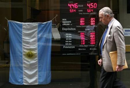 A man walks past an electronic board showing currency exchange rates and an Argentine flag at a money exchange in Buenos Aires, June 1, 2012. REUTERS/Marcos Brindicci