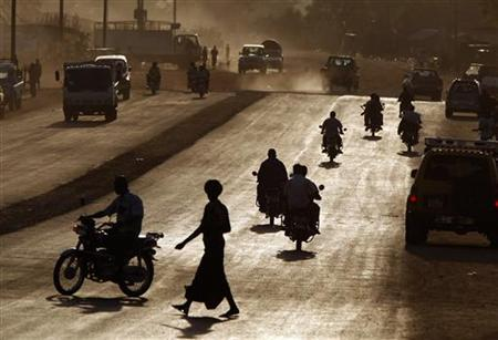 Southern Sudanese men ride motorcycles during sunset in Juba, January 5, 2011. REUTERS/Goran Tomasevic