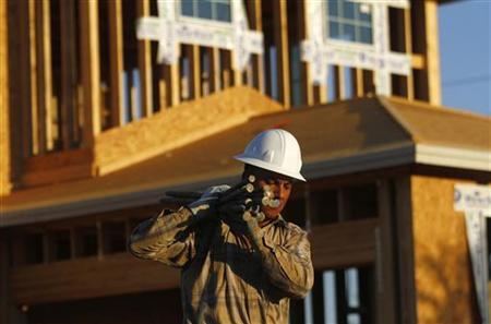 A worker carries materials for a house being constructed in Phoenix, Arizona, August 23, 2011. REUTERS/Joshua Lott