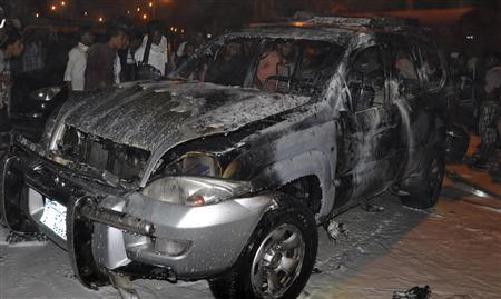 People look at the burnt car of Brigadier Omar Barasheed, the dean of the Command and General Staff College, after a blast ripped through it in the southern Yemeni port city of Mukalla August 9, 2012. REUTERS/Stringer