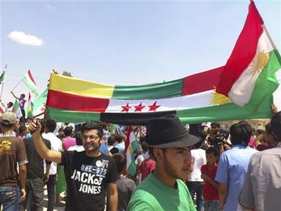 Demonstrators hold Kurdish and Syrian opposition flags during a protest against Syria's President Bashar al-Assad in Kubani, near Aleppo, August 10, 2012. REUTERS/Shaam News Network/Handout