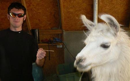Accused Colorado gunman James Holmes gestures next to a llama in this photograph submitted with his application to graduate school at the University of Illinois, in this image released to Reuters on August 10, 2012. REUTERS/University of Illinois Administration/Handout