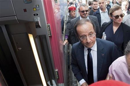 France's President Francois Hollande walks ahead of his companion Valerie Trierweiler as they board a TGV high-speed train at the Gare de Lyon train station in Paris as they depart for their summer holidays August 2, 2012. REUTERS/Julien Muguet