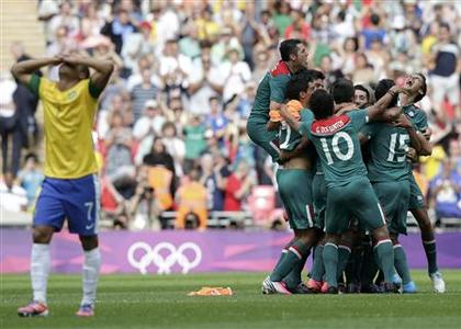 Brazil's Lucas (L) reacts as Mexico's players celebrate their victory over Brazil after their men's soccer final gold medal match at Wembley Stadium during the London 2012 Olympic Games August 11, 2012. REUTERS/Toru Hanai