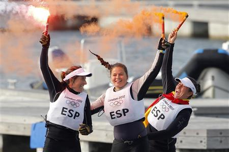Spain's Tamara Echegoyen, Sofia Toro (C) and Angela Pumariega (L) wave flares as they celebrate winning gold in the women's Elliott 6m sailing class at the London 2012 Olympic Games in Weymouth and Portland, southern England, August 11, 2012. REUTERS/Benoit Tessier