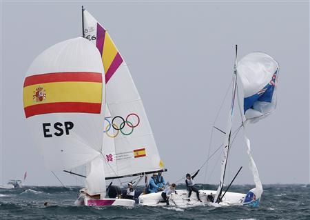 Spain's and Australia's competitors sail during the women's Elliott 6m medal race at the London 2012 Olympic Games in Weymouth and Portland, southern England, August 11, 2012. Australia's Olivia Price (L, in water) fell off the dinghy. REUTERS/Pascal Lauener