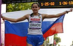 Russa Elena Lashmanova segura bandeira de seu país enquanto comemora a vitória da marcha feminina de 20km nos Jogos Olímpicos de Londres. A russa Yelena Lashmanova conquistou o ouro na marcha feminina de 20km com um tempo recorde de 1h25min2s neste sábado. 11/08/2012 REUTERS/Laszlo Balogh