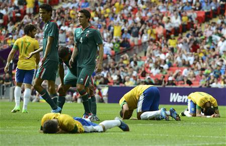 Brazil's players react on the ground after losing to Mexico as Mexico's Diego Reyes (2nd L), Carlos Salcido (3rd L) and Hiram Mier (4th L) walk by after the men's soccer final gold medal match at Wembley Stadium during the London 2012 Olympic Games August 11, 2012. REUTERS/Nigel Roddis