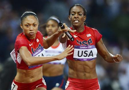 Allyson Felix (L) of the U.S. takes the baton from team mate DeeDee Trotter in the women's 4x400m relay final at the London 2012 Olympic Games at the Olympic Stadium August 11, 2012. REUTERS/Dylan Martinez