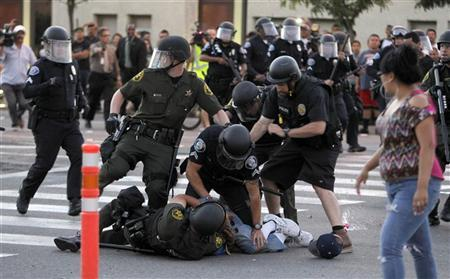 A protester is arrested by police officers from Orange County as protesters try to occupy the the intersection of Anaheim Blvd. and Broadway to demonstrate against recent police shooting in Anaheim, California July 24, 2012. REUTERS/Alex Gallardo
