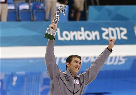 Michael Phelps of the U.S. celebrates with his trophy awarded to him by FINA honouring him as the most decorated Olympian of all time, after winning the men's 4x100m medley relay final during the London 2012 Olympic Games at the Aquatics Centre August 4, 2012. REUTERS/Tim Wimborne