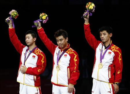 China's Zhang Jike (R) and team mates Wang Hao (C) and Ma Long celebrate winning gold in the medal ceremony of the men's team table tennis tournament at the ExCel venue during the London 2012 Olympic Games August 8, 2012. REUTERS/Darren Staples