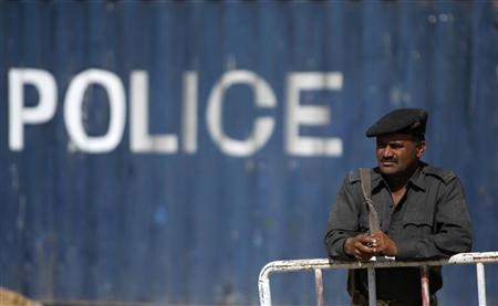 A policeman stands guard at a road which has been blockaded with a container due to increased security measures in Karachi February 17, 2010. REUTERS/Akhtar Soomro