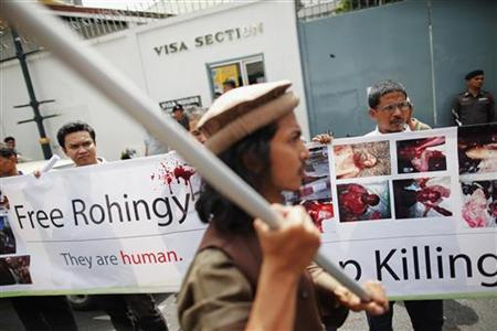 Muslims hold pictures and banners as they protest in front of Myanmar's embassy in Bangkok June 21, 2012. REUTERS/Damir Sagolj/Files