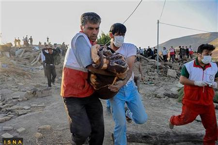 Rescuers recover a body during a search for victims in an earthquake-stricken village in an undisclosed location, northwest Iran August 12, 2012. REUTERS/Roohollah Vahdati/ISNA