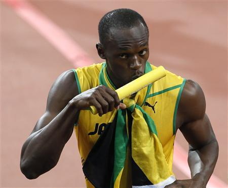 Jamaica's Usain Bolt kisses the baton as he celebrates winning the men's 4x100m relay final during the London 2012 Olympic Games at the Olympic Stadium August 11, 2012. The Jamaican team set a new world record of 36.84 seconds. REUTERS/Stefan Wermuth