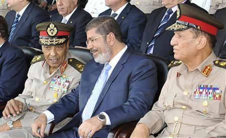 Egypt's new Islamist President Mohamed Mursi (C) speaks with Field Marshal Hussein Tantawi (L) and Egyptian Armed Forces Chief Of Staff Sami Anan during a soldier graduation ceremony at the Egyptian military academy in Cairo in this July 17, 2012 file photo. Mursi ordered Egypt's two top generals to retire, including Hussein Tantawi who led the nation after Hosni Mubarak was ousted, and appointed two generals in their place, the presidential spokesman announced on August 12, 2012. Tantawi, who served Mubarak as a minister for 20 years, and Chief of Staff Sami Enan were both appointed as advisers to Mursi. Spokesman Yasser Ali said the changes among Egypt's top brass were effective immediately. REUTERS/Sherif Abd Monam/Egyptian Presidency/Handout/Files