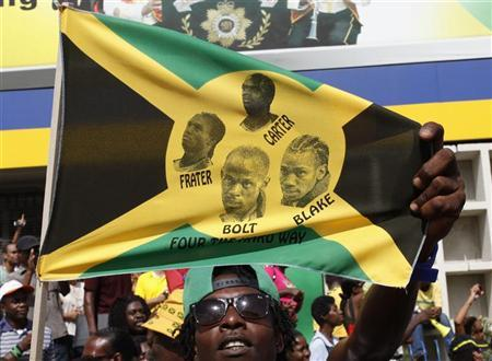 A Jamaican man holds a flag showing the faces of Jamaica's Usain Bolt, Nesta Carter, Michael Frater and Yohan Blake after Jamaica wins the men's 4x100 metres final in the London 2012 Olympics Games, in Half Way Tree, Kingston August 11, 2012. REUTERS/Gilbert Bellamy