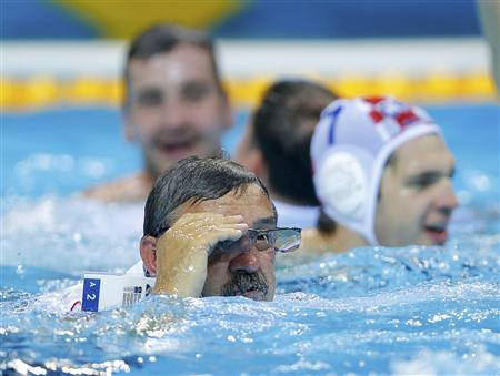 Croatia's head coach Ratko Rudic (C) adjusts his glasses as he celebrates with his players in the water after their team defeated Italy during their men's gold medal water polo match during the London 2012 Olympic Games August 12, 2012. REUTERS/Laszlo Balogh