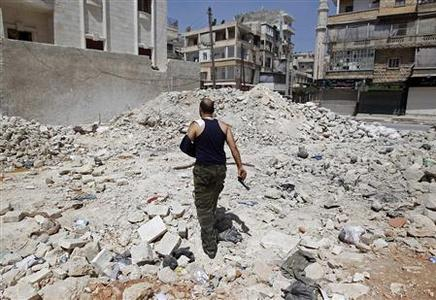 A wounded Free Syrian Army commander walks through rubble in the Salaheddine neighbourhood of central Aleppo August 11, 2012. REUTERS/Goran Tomasevic