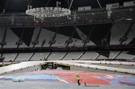 A worker hauls a trolley during the cleanup operation at the London 2012 Olympic stadium after the closing ceremony early August 13, 2012. REUTERS/Chris Helgren