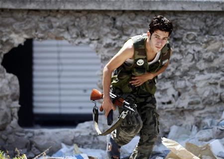 A Free Syrian Army fighter runs for cover during heavy fighting in Salaheddine neighborhood of central Aleppo August 11, 2012. REUTERS/Goran Tomasevic