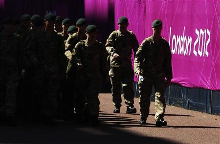 Soldiers patrol past signage for the London 2012 Olympic Games near the beach volleyball courts at Horse Guards Parade in London in this July 24, 2012 file photograph. REUTERS/Luke MacGregor/Files