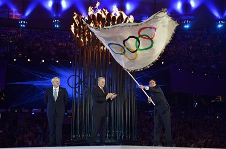 Rio de Janeiro Mayor Eduardo Paes waves the Olympic flag as IOC President Jacques Rogge applauds and London Mayor Boris Johnson watches during the ceremonial handing over of the Olympic flag at the closing ceremony of the London 2012 Olympic Games at the Olympic stadium August 12, 2012. REUTERS/Jeff J Mitchell/Pool