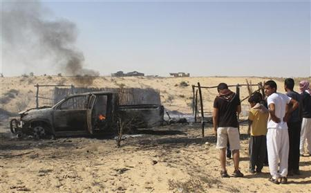 People watch as smoke rises from the burning remains of a building and vehicle after a firefight between Egyptian security forces and suspected militants at the al-Goura settlement in Egypt's north Sinai region, about 15 km (10 miles) from the border with Israel, August 12, 2012. REUTERS/Stringer