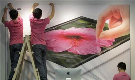 Employees hang a poster advertising the New iPad at an Apple dealership in Wuhan, Hubei province July 19, 2012. REUTERS/Stringer/Files