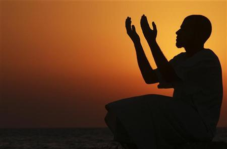 A man raises his hands to pray near the sea at sunset after a day of fasting in the holy month of Ramadan in Benghazi July 24, 2012. Picture taken July 24, 2012. REUTERS/Esam Al-Fetori
