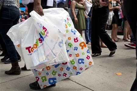A shopper carries bags through Times Square in New York, July 27, 2012. REUTERS/Andrew Burton/Files